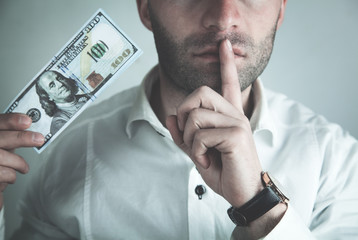 Caucasian businessman making silence gesture and showing money.