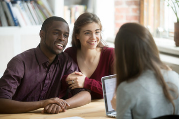 Happy multiracial young couple smiling listening to female real estate agent excited about house purchase together. Husband and wife being emotional about taking bank loan talking to financial advisor