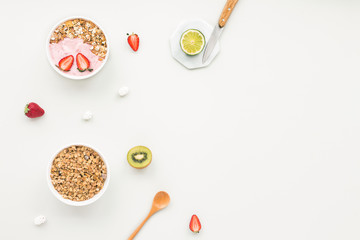 Healthy breakfast with yogurt, muesli, fruits, strawberry on grey background, flat lay, top view