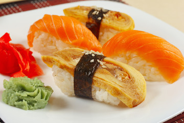 Sushi with omelet with eel and with salmon and ginger and wasabi on a black and red bamboo mat close up.