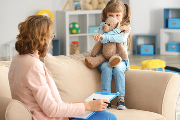 Female psychologist working with cute little girl in office