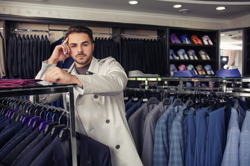 Young man in stylish coat at menswear store