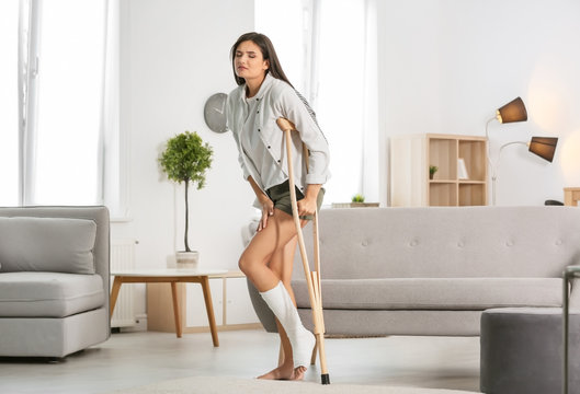 Young woman with crutch and broken leg in cast at home