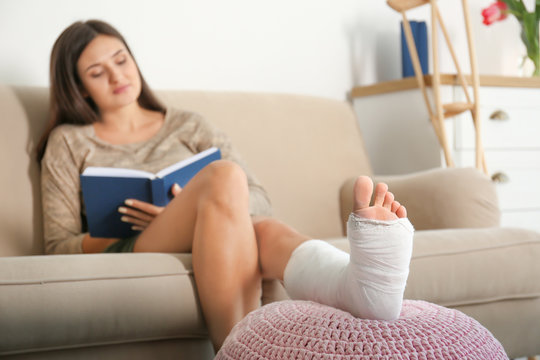 Young woman with broken leg in cast reading book while sitting on sofa at home