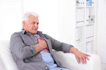 Senior man having heart attack on sofa