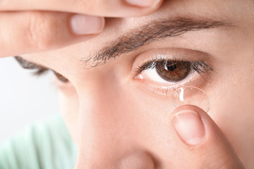 Young woman putting contact lens in her eye, closeup