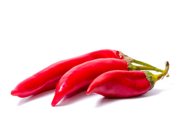 Three red hot chili peppers on a white background. Spices for food. Bright juicy colors.
