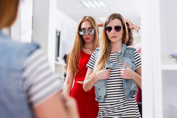 Glamorous girls trying on sunglasses posing in front of the mirror in fashion boutique