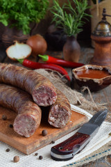 Traditional smoked sausage in a rustic style. Appetizing sausages made of pork and lamb with fresh herbs, spices on the wooden board. Free space for text.