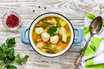 Vegetable meatball soup in a pot on white wooden background. Top view, space for text.