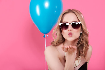 Attractive blonde young woman in elegant party dress and golden jewelry celebrating birthday and blowing a kiss towards camera. Fashion portrait on pastel pink background.