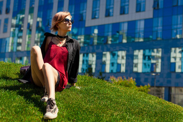 A young hipster girl sits on a green hill in the city.