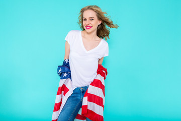 I love America. Happy young smiling woman in jeans and white Tshirt holding American flag and looking at camera while standing against pastel blue background.