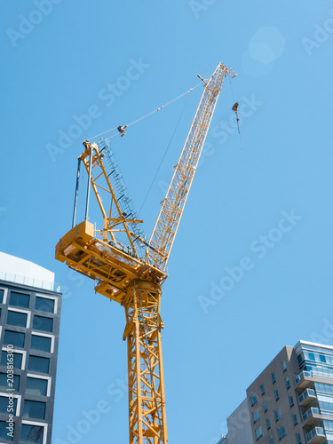A Yellow Tower Crane on Top of A Steel Skeleton Frame  Blue