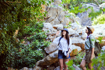 Two beautiful young girls travel in the mountains and enjoy the view of the landscape of green trees.