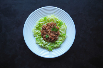 Plate of zucchini spaghetti with beef bolognese on black background.