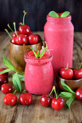 Red smoothie made of cherries in glass jars. Berries are around on a wooden table