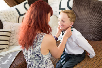 Mother getting son dressed for school at home