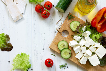 Cooking qreek salad with fresh vegetables, feta cheese and black olives on a white wooden table. Copy space, top view flat lay background.