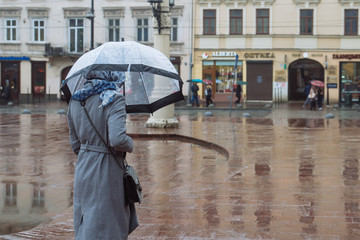 woman walk with transparent umbrella under rain at city street. copy space