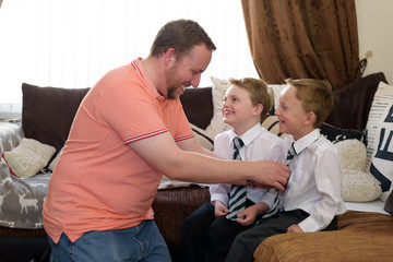 Father getting two sons dressed for school at home