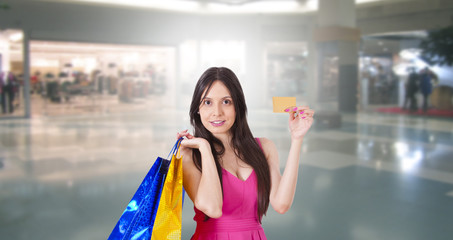 woman buying with credit card and shopping bags