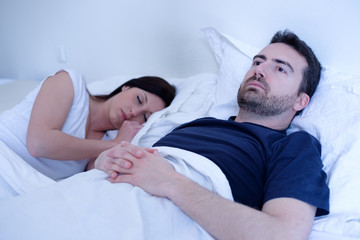 Sad and depressed man lying in the bed with wife