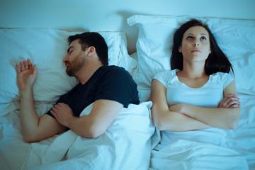 Sad and thoughtful woman awake while husband is sleeping in bed