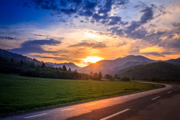 travel photo shoot taken on the road, in a trip, in a summer vacation, at sunset. beautiful summer background with a green nature landscape. scene with hills,trees, colorful sky and sun in summertime