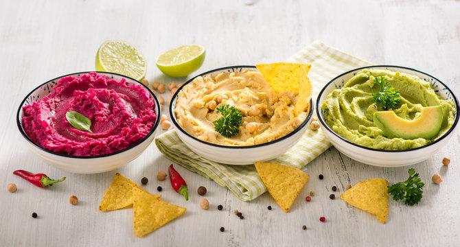 Colorful hummus with vegetables, vegan snack, beetroot and avocado hummus, vegetarian eating