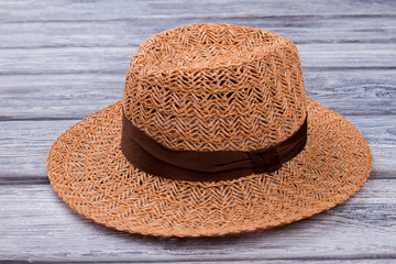 Brown straw hat, close up. Wooden desk surface background.