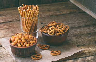 Salty snacks on wooden background. Crackers, pretzel, salted straws, nuts, dried fish. Junk food for beer or cola. Photographed with natural light. Fototapete