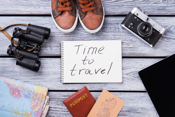 Items for traveling, top view. Flat lay, wooden surface background.