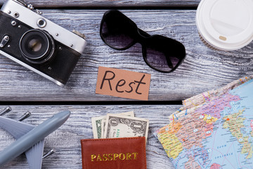 Top view essential rest and travel items. Wooden desk surface background.