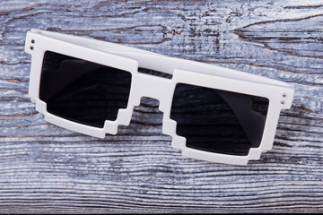 Pixel sunglasses close up. Black eyeglasses with white frame on wooden desk surface.