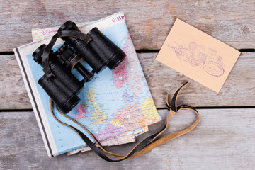 Binoculars upon map and post mail with stamps. Top view, flat lay. Wooden desk surface background.