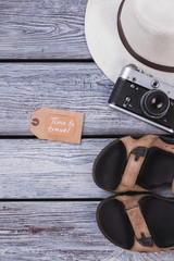 Summer travel accessories for man. Wooden desk surface background.