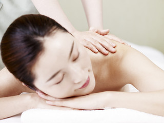 beautiful young asian woman receiving massage in spa salon, focus on masseuse's hands