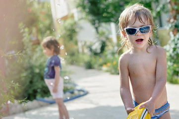 Funny boy in spectacles showing tongue and playing with big shoe near pool