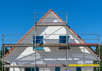 weiße Fassade eines neuen Einfamilienhauses mit Gerüst an der Fassade