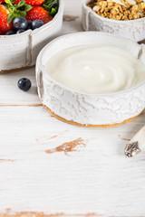 Bowl of natural yogurt with granola and fresh berries