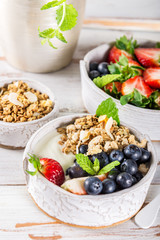 Bowl of natural yogurt with granola and fresh berries