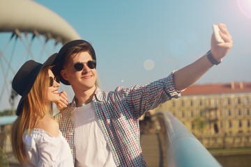 Couple smile on bridge. Tourist having fun on sumer travel adventure vacation. Happy tourists taking photo of themselves on smartphone. Weeknd in Europe, dating concept. Girl in hat and sunglasses