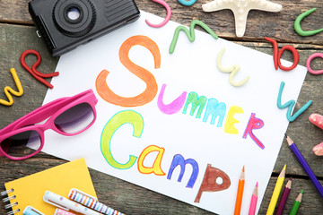 Inscription Summer Camp with sunglasses and retro camera on wooden table