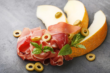Ripe melons with jamon, basil leafs and olives on grey wooden table