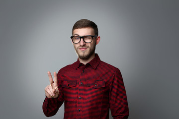 Portrait of young man in glasses on grey background