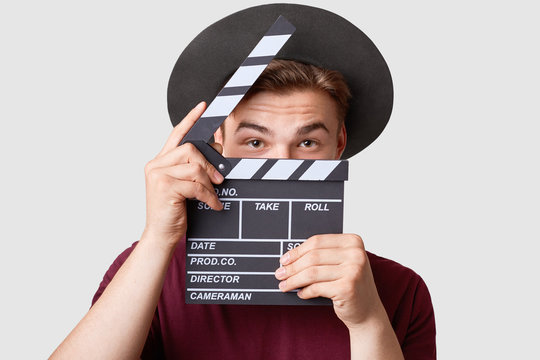Professional male actor ready for shooting film, holds movie clapper, prepares for new scene, wears special clothes, isolated on white background. Handsome young man poses with clapboard in studio