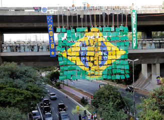Brazilian climbers go for the world record of largest rappel mosaic as they form the Brazilian flag with an image of the World Cup trophy at Sumare bridge in Sao Paulo