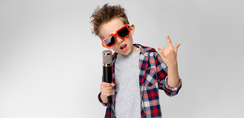 A handsome boy in a plaid shirt, gray shirt and jeans stands on a gray background. A boy wearing sunglasses. The boy holds a microphone in his hand. The boy shows a rocker goat.