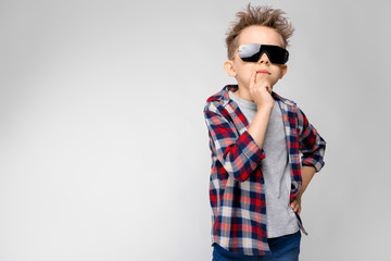 A handsome boy in a plaid shirt, gray shirt and jeans stands on a gray background. The boy in black sunglasses. The boy put a finger to his mouth